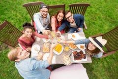 Lyckliga vänner som har matställen på det trädgårds- partiet för sommar Royaltyfri Foto