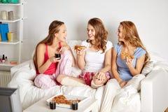 Lyckliga vänner som hemma äter pizza och håller ögonen på tv Royaltyfri Foto