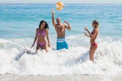 Lyckliga vänner som spelar med en beachball i havet Arkivbilder