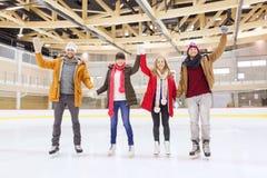 Lyckliga vänner som vinkar händer på att åka skridskor isbanan Arkivfoto