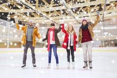 Lyckliga vänner som vinkar händer på att åka skridskor isbanan Royaltyfria Foton