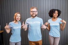 Lyckliga volontärer inomhus royaltyfri bild