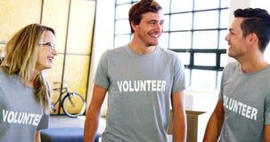 Lyckliga volontärer som påverkar varandra med de