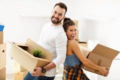 Lyckliga vuxna par som är rörande ut eller in till det nya hemmet Royaltyfri Foto