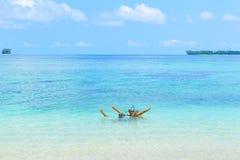 Lyckliga vuxna par som har gyckel i turkosvatten som bär snorkla maskeringen Verkligt folk som badar i det karibiska havet på den royaltyfri foto