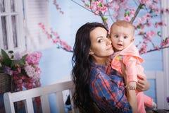 lyckligt älska för familj Den gulliga lilla flickan kammar hennes hår för moder` s fotografering för bildbyråer