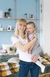 lyckligt älska för familj Den unga blonda modern som spelar med henne, behandla som ett barn i sovrummet Arkivbilder