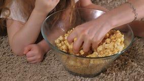 lyckligt älska för familj Modern och hennes dotterbarnflicka äter popcorn på golvet i rummet framdel av TV:N arkivfilmer