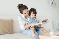lyckligt älska för familj Nätt ung asiatisk moder som läser en bok till royaltyfri foto