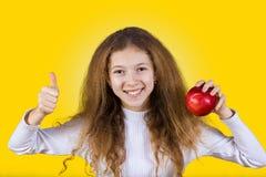 Lyckligt är att le lilla flickan som rymmer ett rött äpple och tummen upp royaltyfria foton