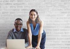 Lyckligt affärsfolk på ett skrivbord genom att använda en dator mot den vita väggen Royaltyfria Bilder
