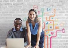 Lyckligt affärsfolk på ett skrivbord genom att använda en dator mot den vita väggen med diagram Royaltyfria Foton