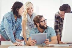 Lyckligt affärsfolk som använder den digitala minnestavlan på datorskrivbordet Fotografering för Bildbyråer