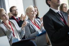 Lyckligt affärsfolk som applåderar under seminarium Arkivfoton