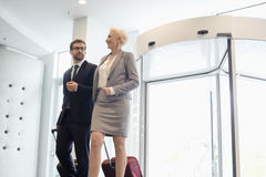 Lyckligt affärsfolk som drar bagage, medan gå i konventcentrum Royaltyfri Foto