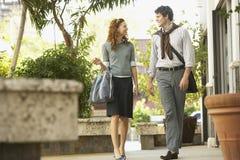 Lyckligt affärsfolk som går på trottoaren arkivbild