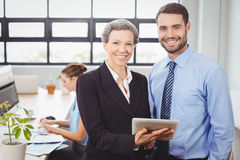 Lyckligt affärsfolk som i regeringsställning använder den digitala minnestavlan Arkivbilder