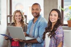 Lyckligt affärsfolk som i regeringsställning använder teknologier royaltyfria foton