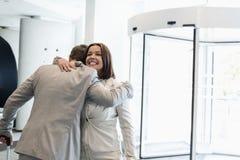 Lyckligt affärsfolk som omfamnar på den ljust tända konventcentret fotografering för bildbyråer