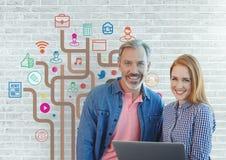 Lyckligt affärsfolk som rymmer en dator mot den vita väggen med diagram Arkivfoto