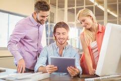 Lyckligt affärsfolk som ser den digitala tabellen Royaltyfri Fotografi