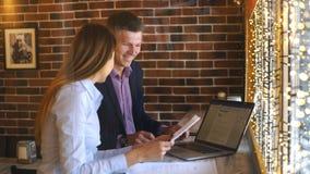 Lyckligt affärsfolk som tillsammans arbetar på bärbara datorn stock video