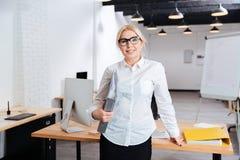 Lyckligt affärskvinnaanseende och hållande mappar på kontoret Royaltyfria Bilder