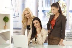 Lyckliga kontorsarbetare som är funktionsdugliga på datoren på kontoret fotografering för bildbyråer