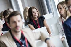 Lyckligt affärskvinnasammanträde med kollegor i seminariumkorridor fotografering för bildbyråer