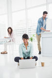 Lyckligt affärskvinnasammanträde på golvet genom att använda bärbara datorn Arkivfoton
