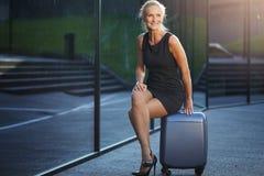 Lyckligt affärskvinnasammanträde på resväskan royaltyfria bilder