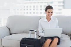 Lyckligt affärskvinnasammanträde på soffan genom att använda bärbara datorn Arkivbilder
