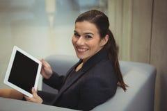 Lyckligt affärskvinnasammanträde på soffan och använda den digitala minnestavlan Fotografering för Bildbyråer