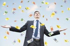 Lyckligt affärsmananseende i regnet av pengar Royaltyfri Foto