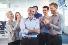 Lyckligt affärsmananseende med korsade armar medan applådera för kollegor arkivbilder