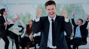 Lyckligt affärsmanStanding In Front Of His Colleagues In kontor arkivbild