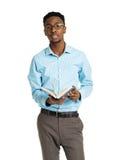 Lyckligt afrikansk amerikanhögskolestudentanseende med boken i hans arkivbild