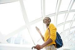 Lyckligt afrikansk amerikankvinnaanseende med bagage och mobiltelefonen på flygplatsen fotografering för bildbyråer