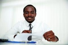 Lyckligt afrikanskt mansammanträde på tabellen royaltyfria foton