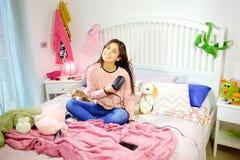 Lyckligt amerikanskt sammanträde för ung kvinna i säng som torkar långt hår som ler sned bollskottet Arkivbild