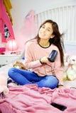 Lyckligt amerikanskt sammanträde för ung kvinna i säng som torkar långt le för hår Fotografering för Bildbyråer