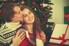 Lyckligt anbud som älskar par i omfamning, värme på julgranen Royaltyfri Fotografi