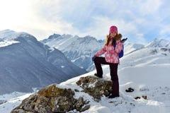 Lyckligt anseende för tonårs- flicka på en sten som ler i snöig berg royaltyfria bilder
