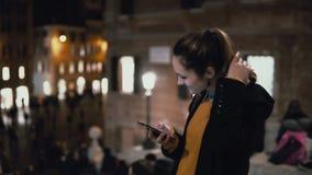 Lyckligt anseende för ung kvinna i folkmassa och användasmartphone Flicka som går och pratar med vänner i afton stock video