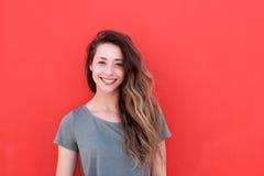 Lyckligt anseende för ung kvinna mot röd bakgrund royaltyfri foto