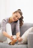 Lyckligt applicera för ung kvinna spikar polermedel, medan tala mobiltelefonen Royaltyfria Bilder