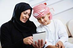 Lyckligt arabiskt barn hemma med hans moder Fotografering för Bildbyråer