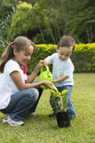 Lyckligt arbeta i trädgården för barn Arkivfoton