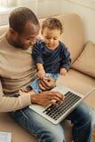 Lyckligt arbete och babysitting för pappa arkivfoto