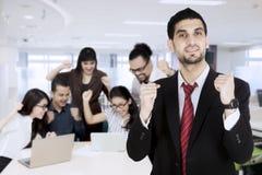 Lyckligt asiatiskt affärsfolk som ser bärbar datordatoren med deras chefanseende på framdelen royaltyfri fotografi